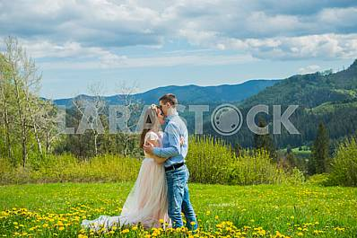 Wedding in mountains, a couple in love, mountains background, standing surrounded dandelions, among the lawn with the green grass, rustic style, girl in long tulle dress, romantic landscape, hugging