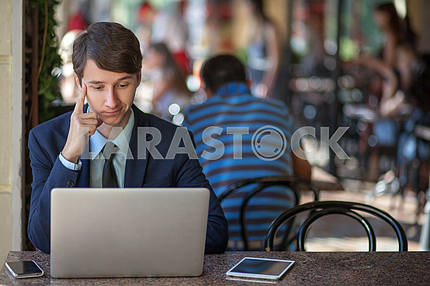 One relaxed young handsome professional businessman working with his laptop, phone and tablet in a noisy cafe. speak with phone.