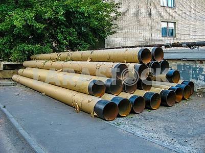 Большие водопроводные трубы лежат на земле.