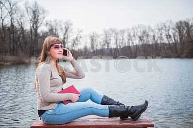 Young Woman speaking by the phone, with book on her hands, daily lifestyle, river on the background, spring, sunny day, sliming