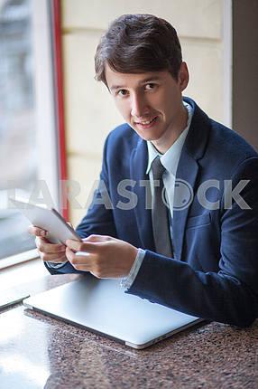 Один расслабленной молодой красивый профессиональный бизнесмен, работающий со своим ноутбуком , телефон и планшет в шумном кафе . говорить с телефоном .