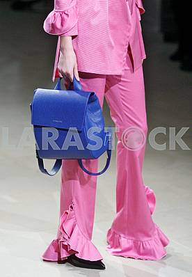 Model in a pink dress holding a blue bag during a demonstration dress by Ukrainian designer Maryana Steshenko
