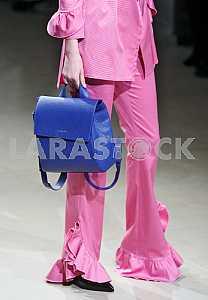 Model in a pink dress holding a blue bag during a demonstration dress by Ukrainian designer Maryana Steshenko