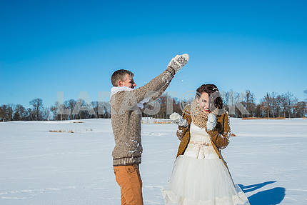 Young wedding couple playing in snow on a sunny winter day. Rustic style wedding. lovely girl in short wedding white dress, blue sky on the background. Brown style wedding