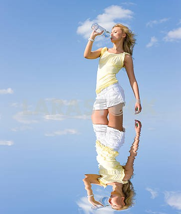 Beautiful girl drinking water against blue sky 2