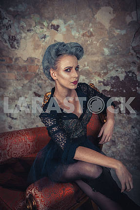 Woman dressed like a vampire - for halloween party, sitting at the vintage arm-chair near  old brick wall . Short black tulle-skirt on a vampire-girl. looking angry like a devil