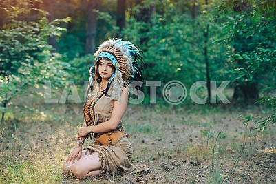 Beautiful girl in a suit of the American Indian sitting in the forrest  in the roach