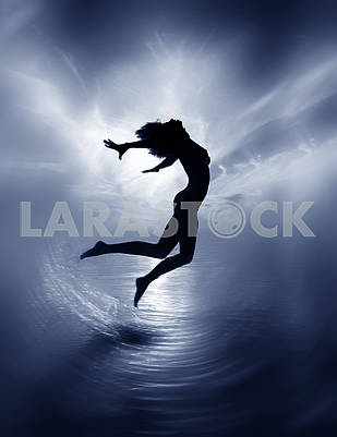 Monochrome image of a naked girl jumping out of the water