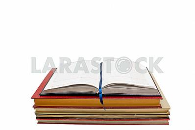 Open notebook on a pile of books, white background