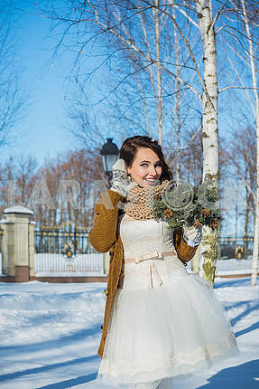 Beautiful bride on a sunny winter day behind the birch. snowy weather. blye sky and trees on the background. Girl in a short wedding dress, rustic style. smiling