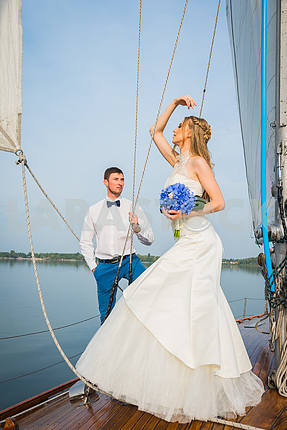 Stylish young bride and groom standing on board the yacht