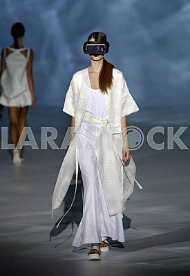 Model c mobile phone attached to the face demonstrates outfit by Ukrainian designer Olena Dats