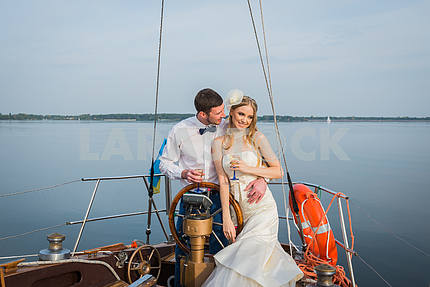 Happy bride and groom hugging on a sailing yacht with the champagne  in their hands on a sunny day; stylish, long dress, bow tie. The steering wheel of the yacht.