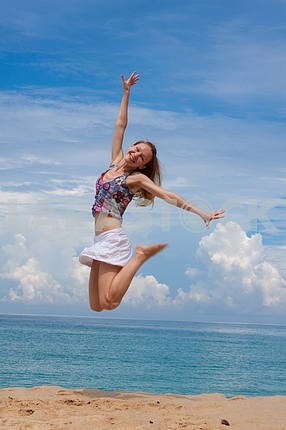 Happy young woman jumping on the background of the azure sea