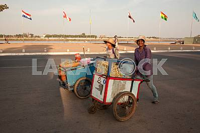 Two girls with wheelbarrows for sale