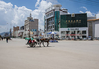 A cart with a horse rides through the central square of the city.