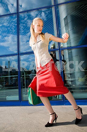 Beautiful girl, blond, runs against the backdrop of the station.