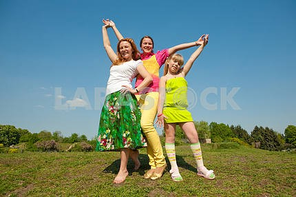 Mother and two daughter jumping on green meadow