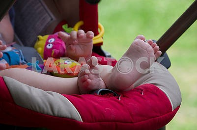 The child sits in a stroller with legs stretched up