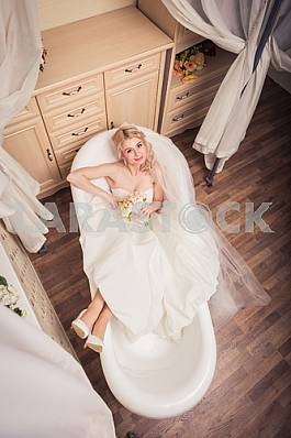 Blonde bride in wedding dress lying in bath, eyes up,