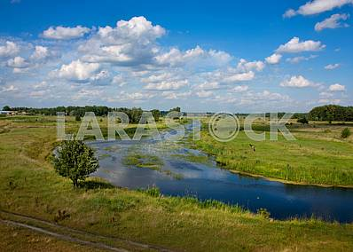 Summer landscape with a river on background sky