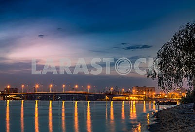 Beautiful background sunset on the river with views of the illuminated lights Bridge