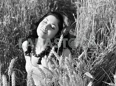 Girl in a wheat field under the sun