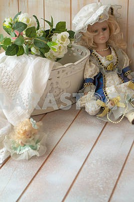 Vintage porcelain doll in the shabby background. Porcelain doll in vintage interior.