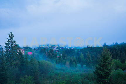 spring in the Carpathian mountains, Ukraine, foggy evening, view from high above, a little city and forrest hills on the landscape