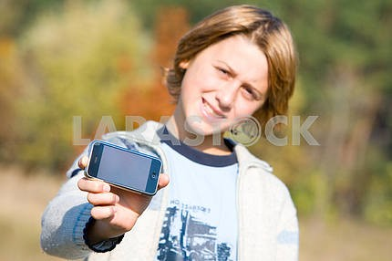 Boy Showing Phone Outdoors. Soft focus.