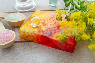 A piece of organic handmade body soap. Red and yellow bright souvenir soap with yellow flowers
