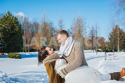 Wedding couple in a showy wither day, holding each other, having fun dansing. rustic style  short wedding dress. Girl brunette. beautiful bride winter lanscape on the background