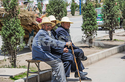 Three old Chinese old man sitting on a bench.