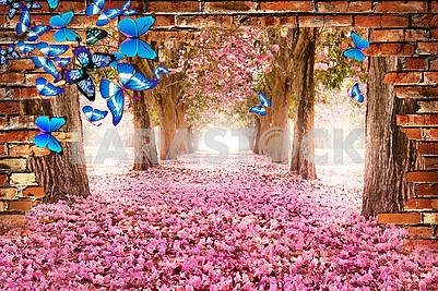 An alley with pink flowers can be seen through the brick wall