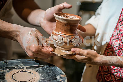 The potter gives the child to his pitcher made on potter's wheel