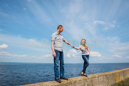 A couple in love - standing together, holding with the hands, near the water on a sunny day, blue sky with long white clouds on the background. men and women are looking into each other, smiling.
