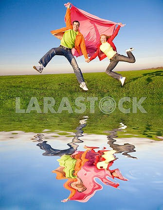 Happy young couple  jumping in sky above a green meadow.Reflecte