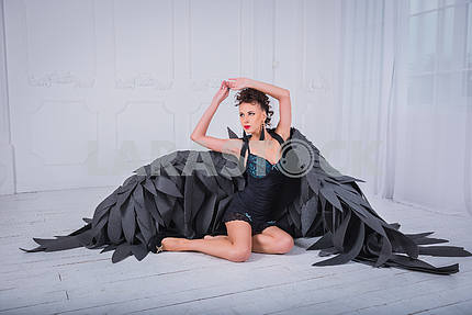 Brunette woman - black angel with the big wings, red lips, black short suit, in white room  sitting on the floor