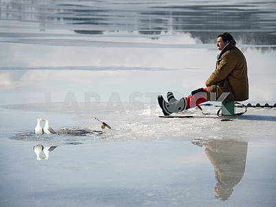 Angler in red pants sits on winter fishing