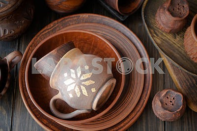 Rustic handmade ceramic clay brown terracotta cups, plates, bowls. Top view.