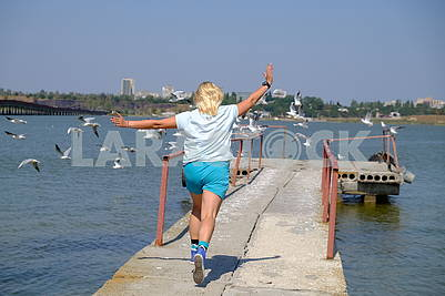 The girl is running on the pier