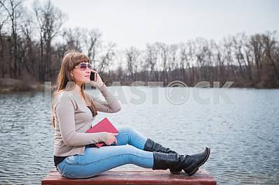 Young Woman speaking by the phone, with book on her hands, daily lifestyle, river on the background, spring, sunny day