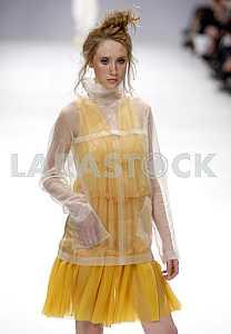 The model in yellow dress demonstrates outfit by Ukrainian designers VOROZHBYT&ZEMSKOVA