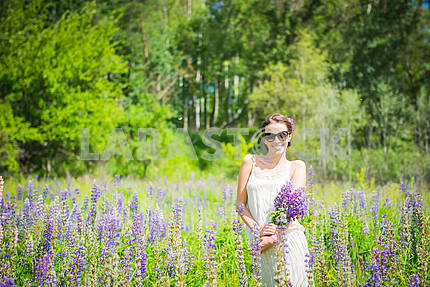 Young woman, happy, standing among the field of violet lupines, smiling, purple flowers. forrest on the background. Summer, sunny day,