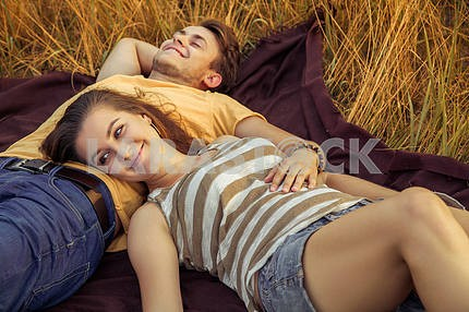 Young fashion beautiful loving casual style couple  lying down on floral field in autumnal park, warm sunny day, enjoying family, romantic date, happiness and love concept.
