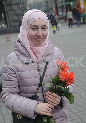 Участница акции держит цветы