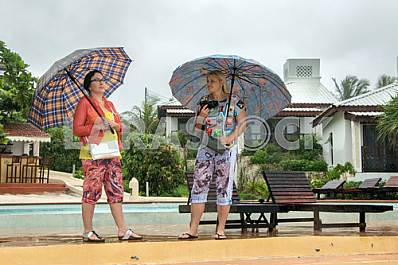Tourists with umbrellas in the pool background photographed in rainy season