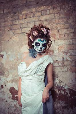 Attractive young woman with sugar skull makeup. Beautiful woman in makeup traditional Mexican Calavera skull Katrina, standing near the old brick wall  with the roses in her hair