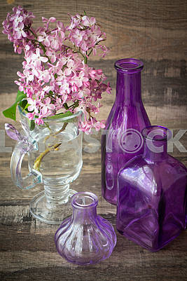 Branch of blooming lilac in a glass bottle with violet bottles decoration