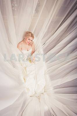 Blonde Bride in wedding dress lying in the bath with bouquet among the veil